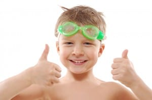 smiling elementary 5 year ols boy with wet hair, goggles and thumbs up over white